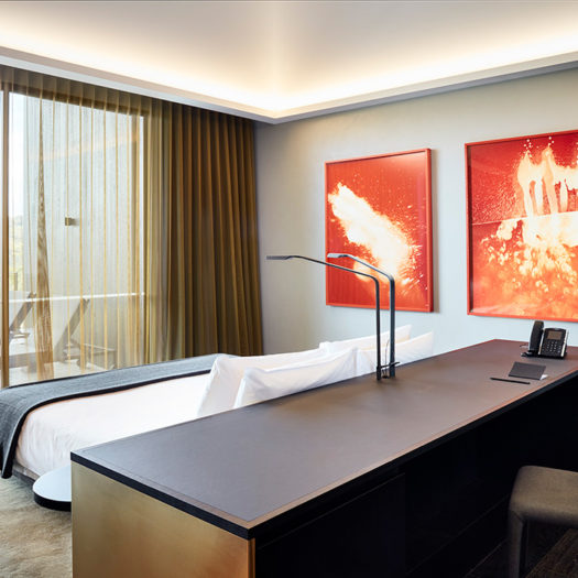 Hotel room with bright orange artwork - example of hotel/ restaurant photography by Rhiannon Slatter