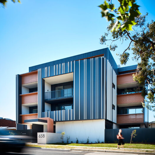 Bayswater Women's Housing view of apartment building from across road with figure on footpath and passing traffic - building photographer example / concept