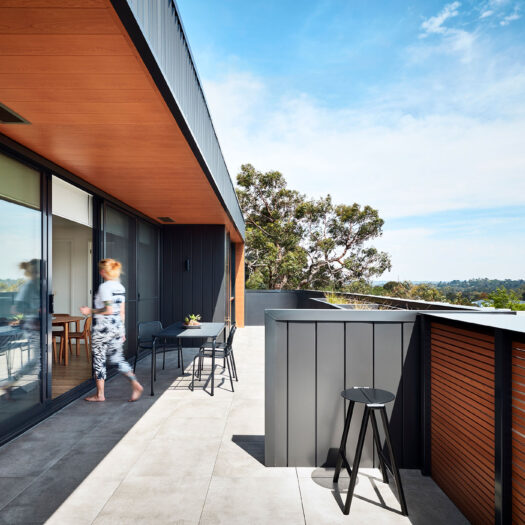 Bayswater Women's Housing elevated balcony view with figure entering sliding glass doors - building photographer example / concept