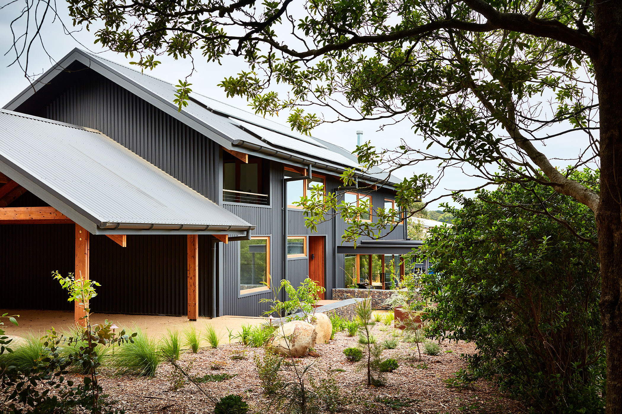Main Ridge Barn barn like house viewed through trees - building photographer example / concept