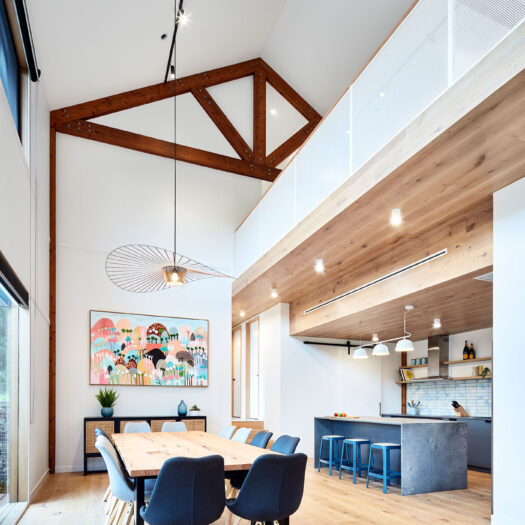 Main Ridge Barn dining high celing with timber trusses across dining table to kitchen with feature blue - building photographer example / concept