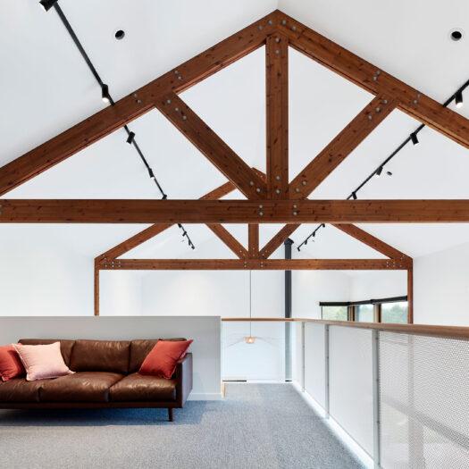 Main Ridge Barn retreat mezzanine with dominant timber trusses photography 10