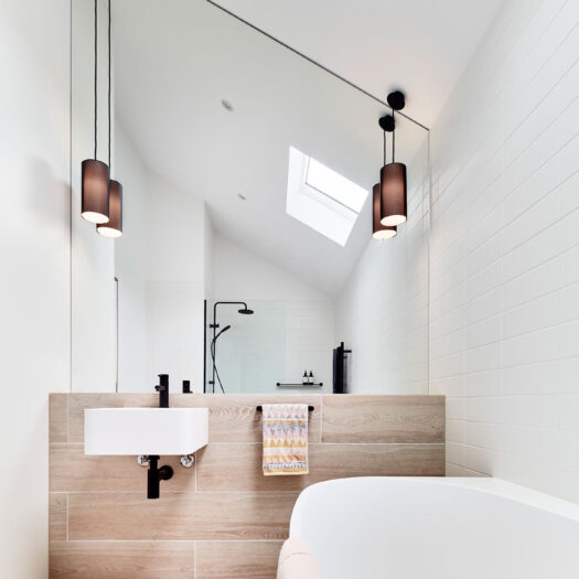 Main Ridge Barn bathroom vanity with timber look tiles across bath and with two pendant lights - building photographer example / concept