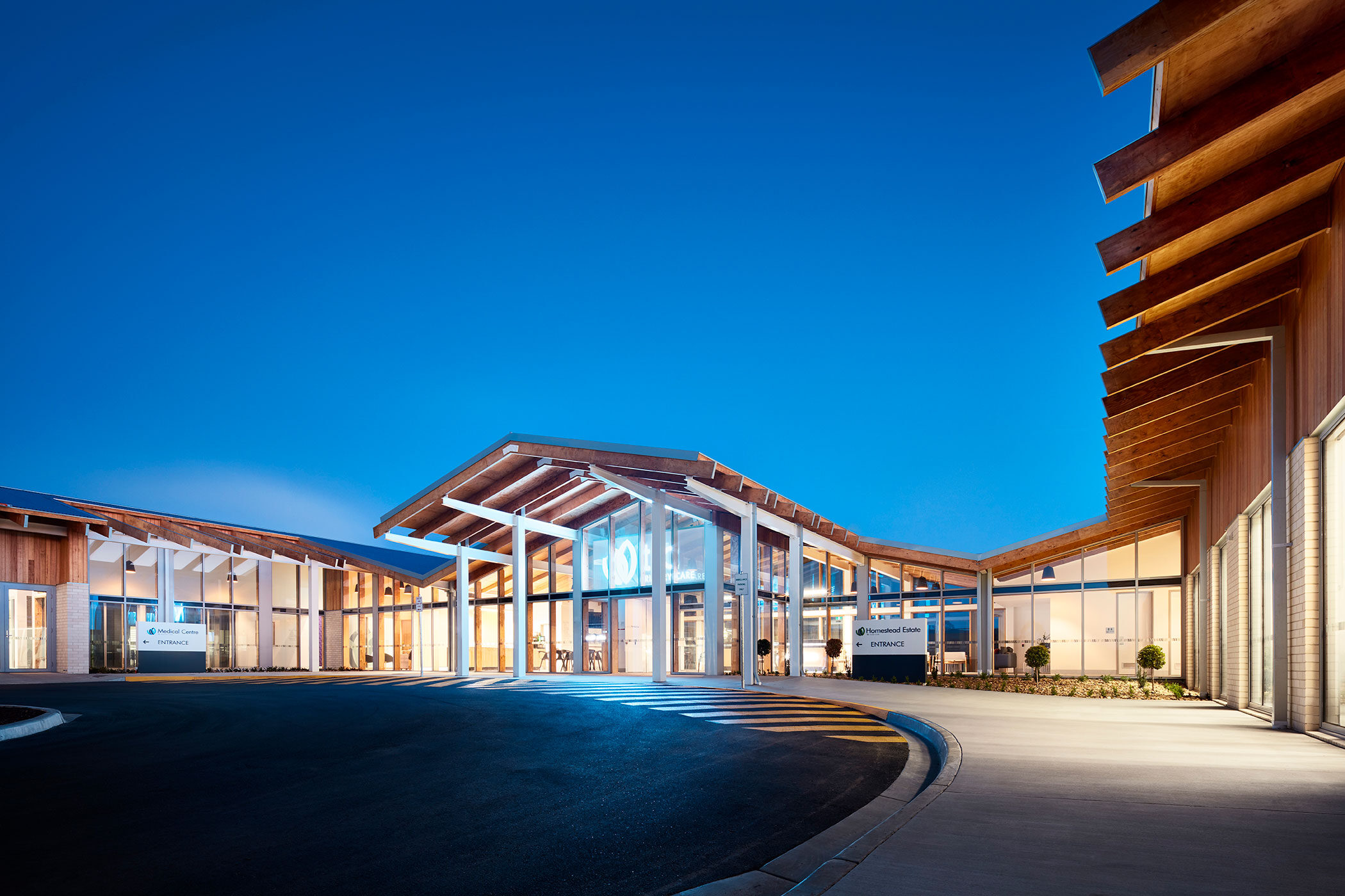 TLC Aged Care Homestead Estate dawn view across main building entry with timber beams and feature light signage - building photographer example / concept