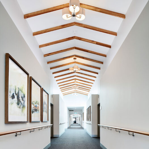 TLC Aged Care Homestead Estate hallway with handrails, high ceiling and timber features - building photographer example / concept