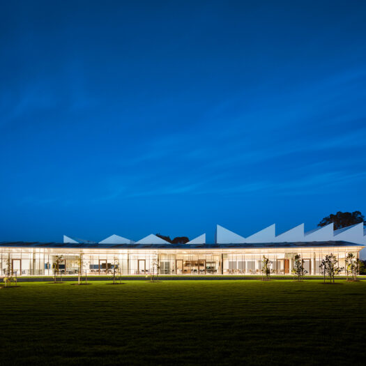 Nunawading Community Hub glazed facade at night with asymmetric sawtooth roofline rising up behind - structure photographer example / concept