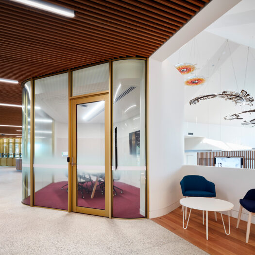 Nunawading Community Hub enclosed glass meeting room from hallways with public seating and artwork hanging from ceiling - structure photographer example / concept