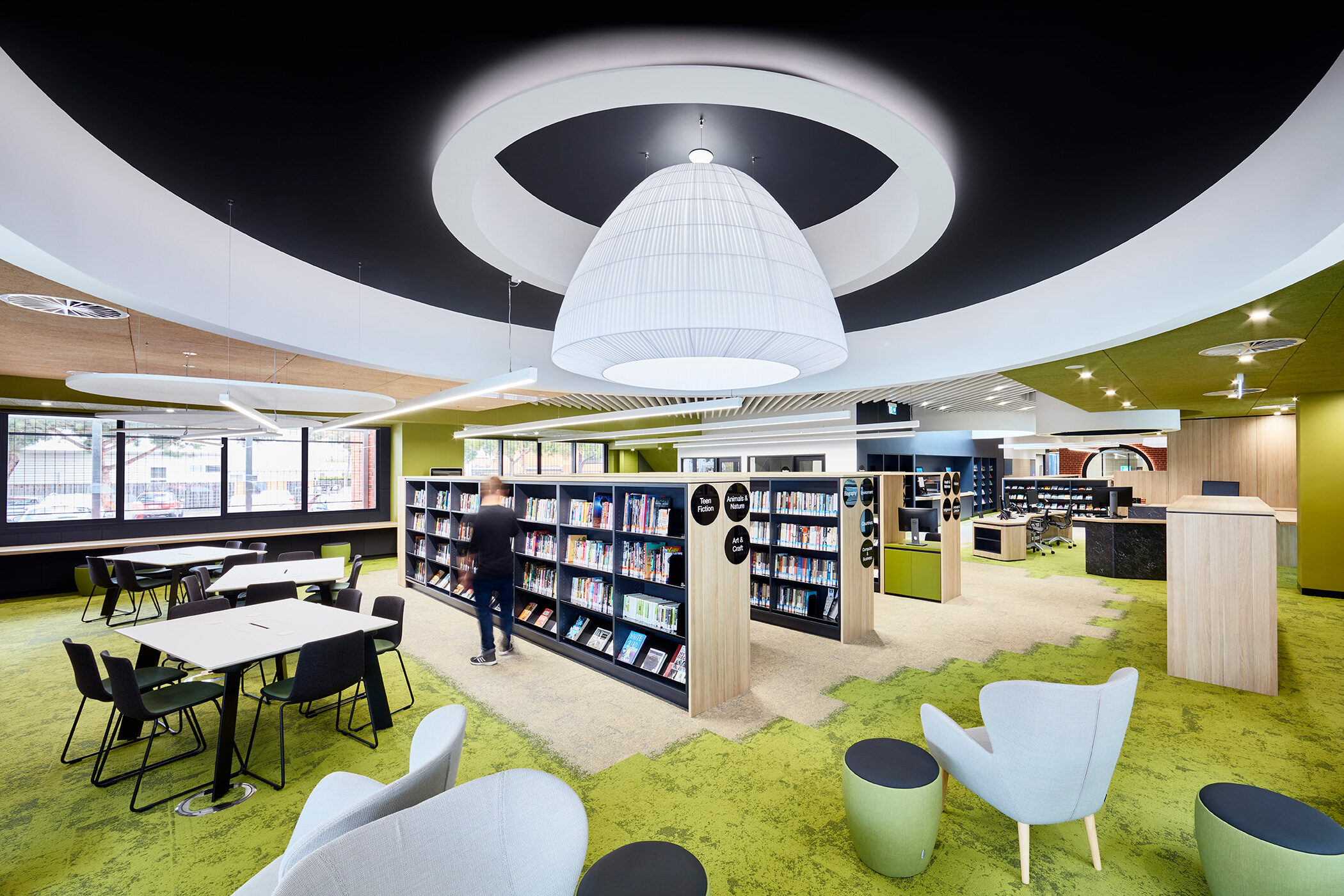 Sandringham Library large pendant light and circular ceiling feature, green carpet and person perusing bookshelves - Interior photography example / concept