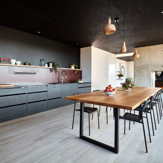 kitchen with black cabinets, timber table and fireplace - building photographer example / concept