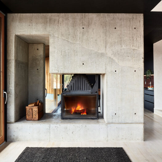 concrete fireplace with roaring fire - building photographer example / concept