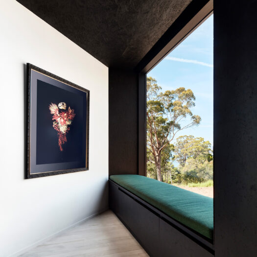 dark green soft window seat with view to trees, artwork on left - building photographer example / concept