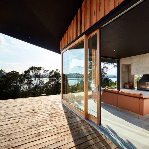 timber deck with streaming sunlight and view to river - building photographer example / concept
