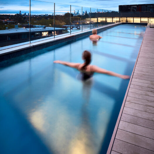 Hawthorn Park rooftop pool at dusk with two people swimming - building photographer example / concept