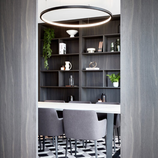 Hawthorn Park view through doors into private dining room with dark timber shelves and decorative items - building photographer example / concept