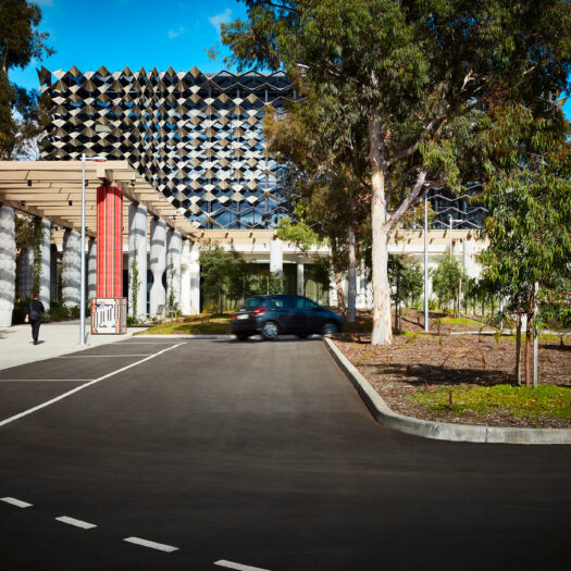 Monash University Chancellery front on view of vehicle entry side of building with red mosaic artist column - University example / concept