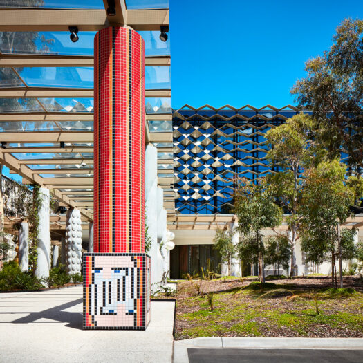 Monash University Chancellery red tile mosaic artist column with building in background - University example / concept