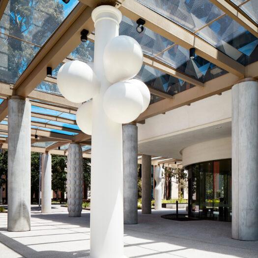 Monash University Chancellery white bubble artist column looking through other columns to campus - University example / concept