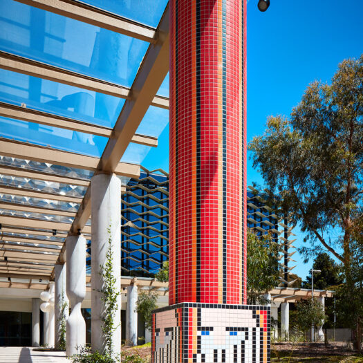 Monash University Chancellery red tile mosaic artist column looking through colonnade to building - University example / concept