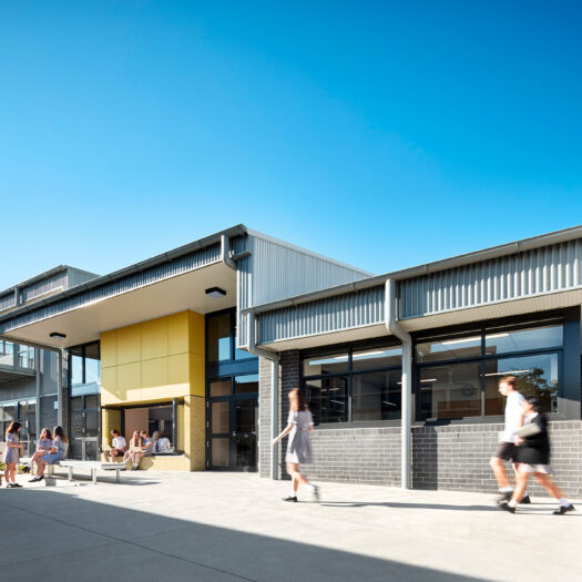 Ringwood Secondary College view of school building with brck wall, yellow window seat and students collaborating - High School photography example / concept