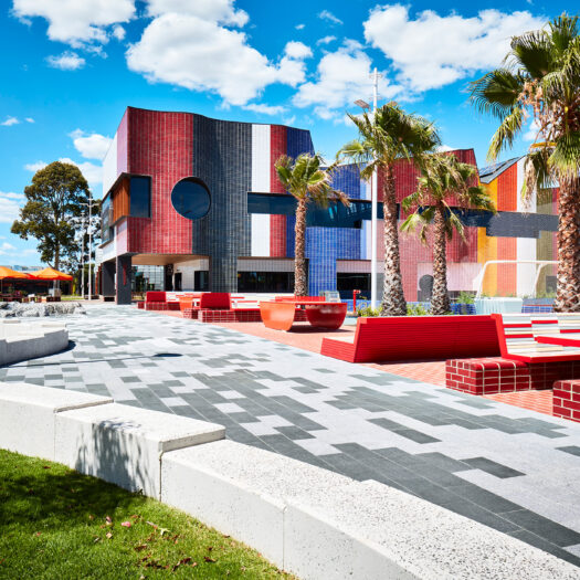 Springvale Library and Community Hub red ourdoor communal tiles and paving with rainbow building - structure photographer example / concept