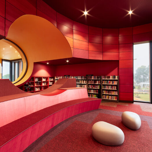Springvale Library and Community Hub red interior with yellow round window with books on shelves - structure photographer example / concept